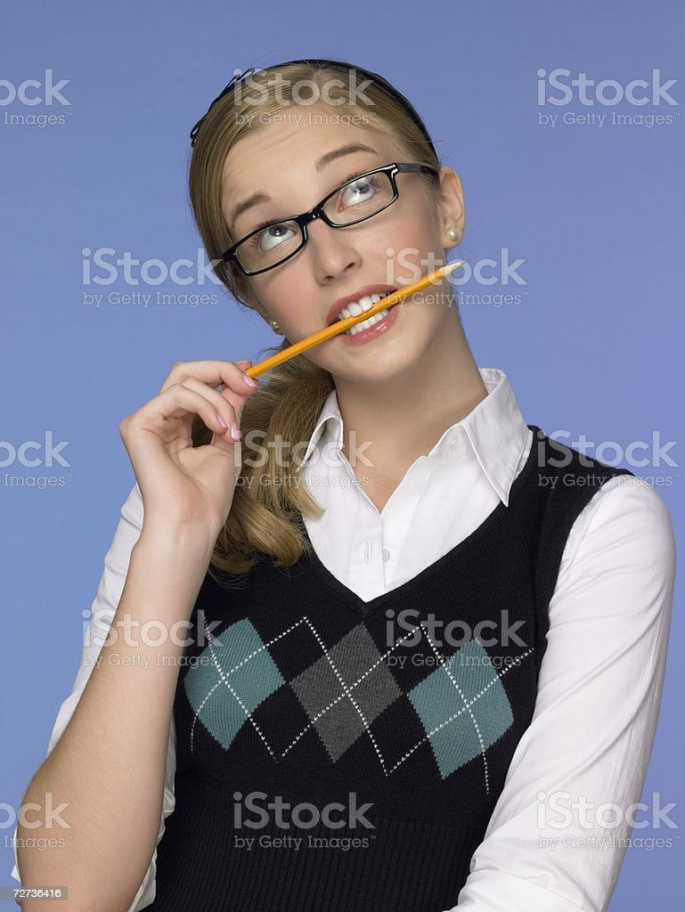 Thoughtful girl biting a pencil royalty-free stock photo