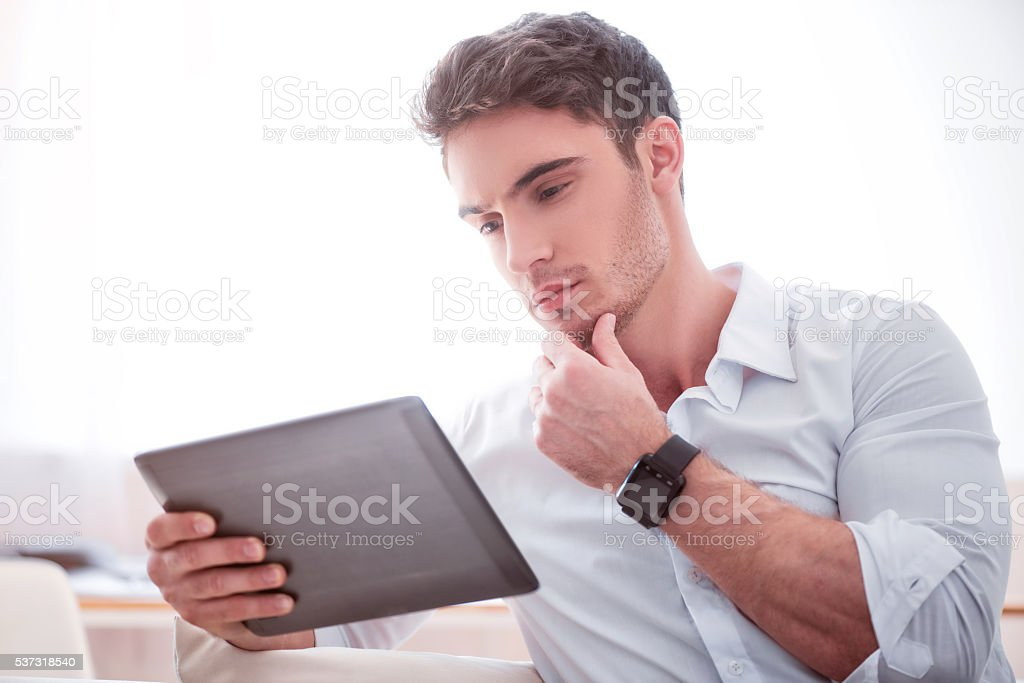 Thoughtful  handsome man using tablet stock photo