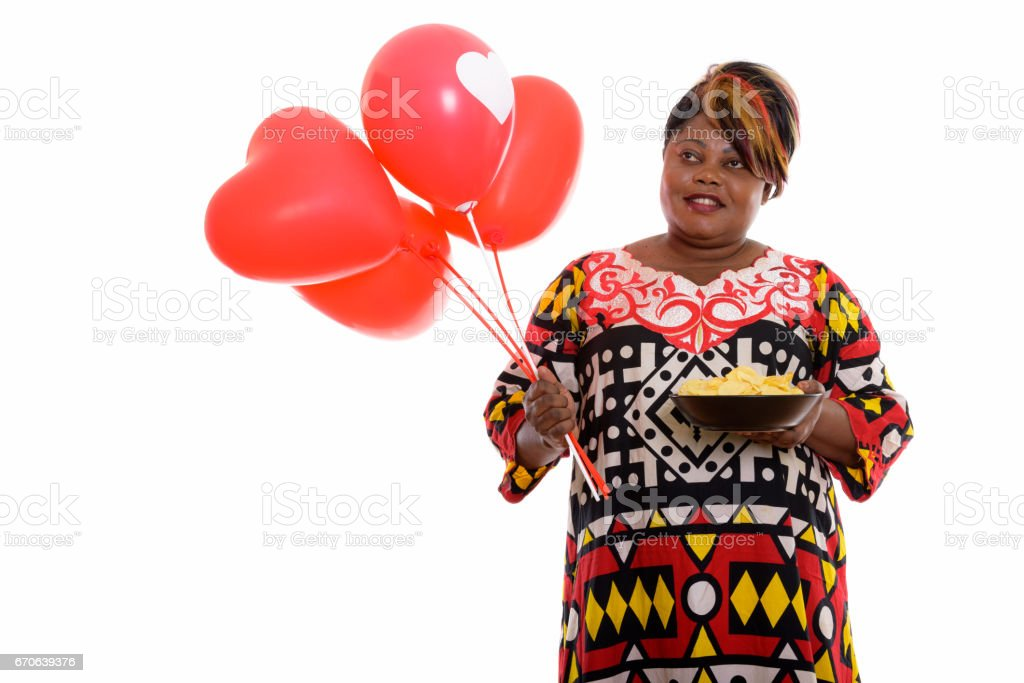Thoughtful happy fat black African woman smiling while holding bowl of potato chips and bunch of red balloons with heart sign stock photo
