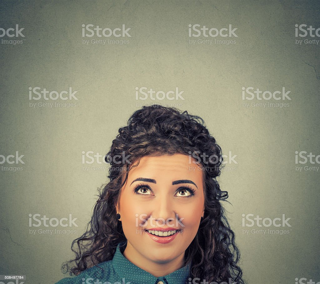 Thoughtful happy woman looking up stock photo