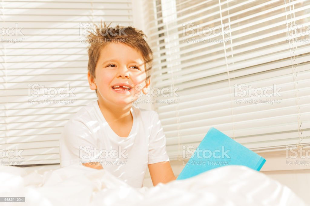 Thoughtful kid boy sitting in his bed with a book stock photo