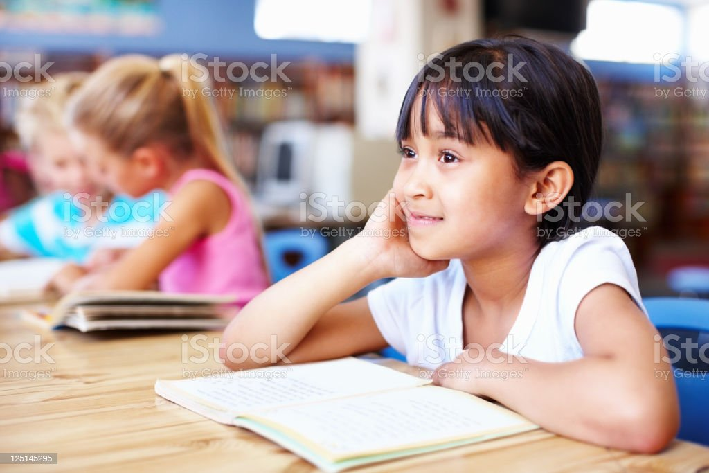 Thoughtful, little girl with friends in the library royalty-free stock photo