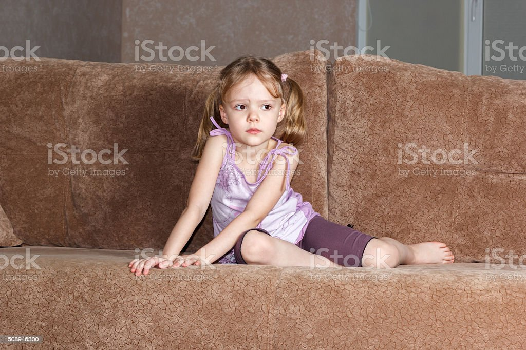 thoughtful little girl with pigtails sitting on couch stock photo