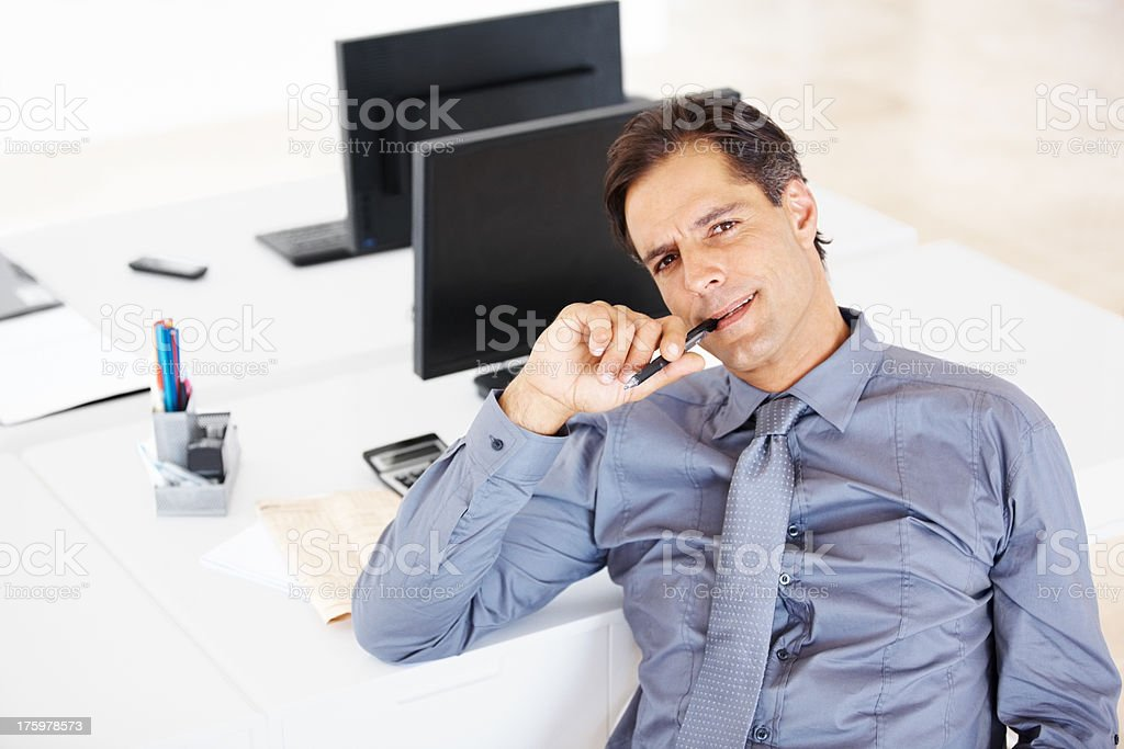 Thoughtful male business executive at his desk stock photo