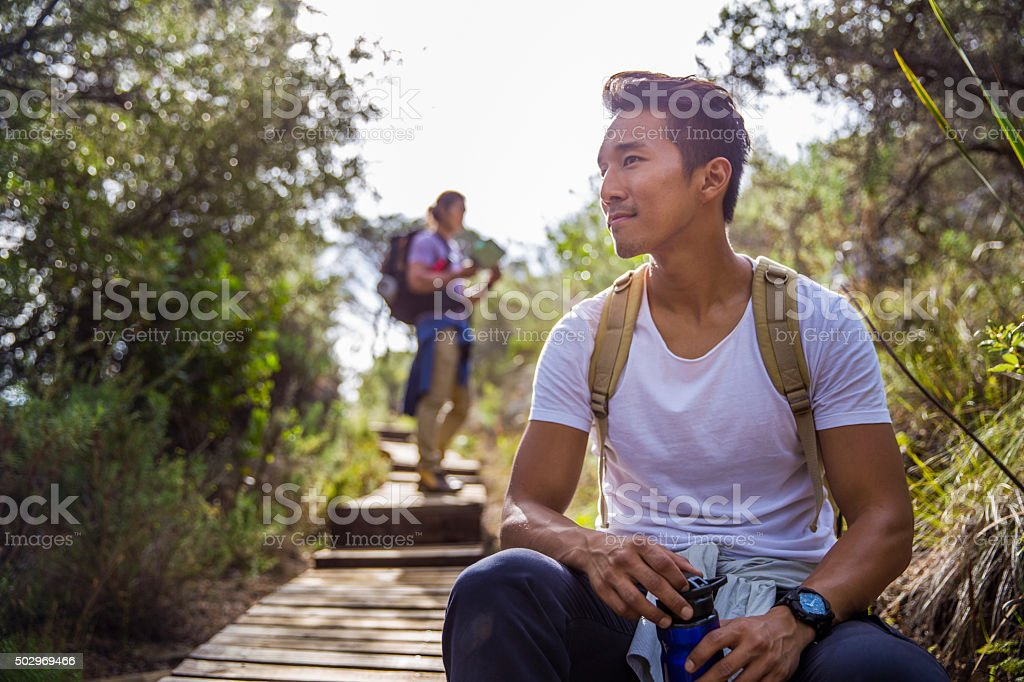 Thoughtful male hiker looking away in forest stock photo