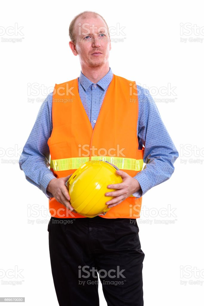 Thoughtful man construction worker holding safety helmet with both hands stock photo
