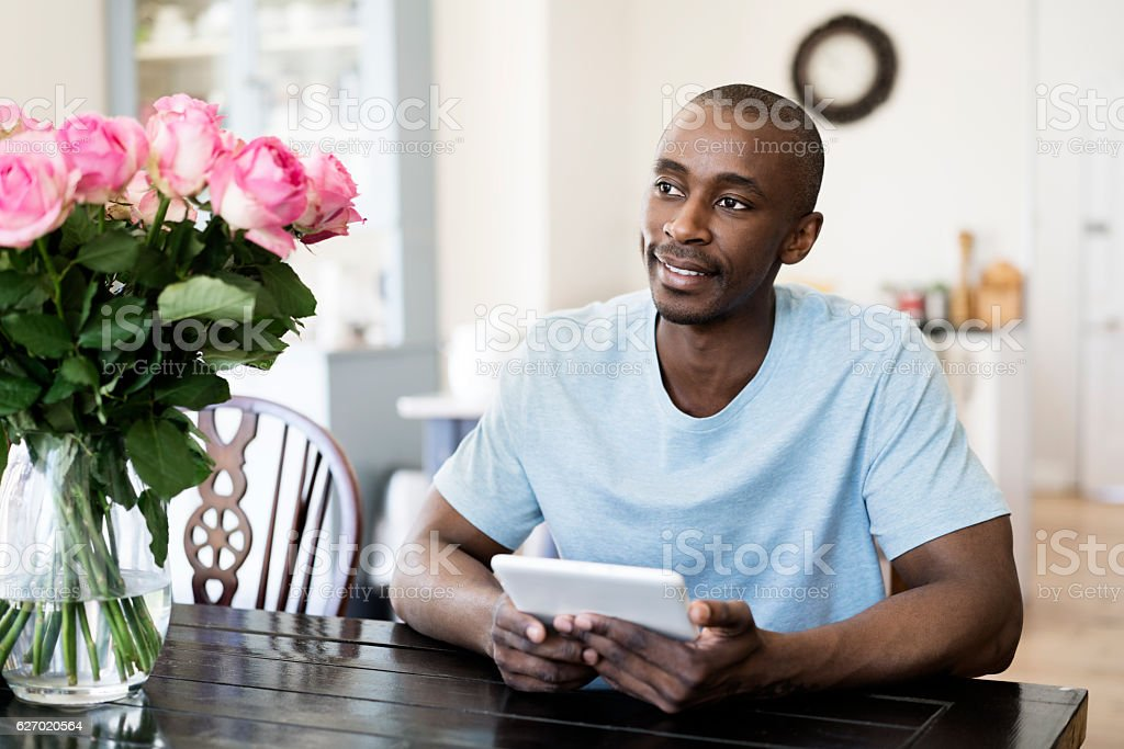 Thoughtful man holding digital tablet at home stock photo