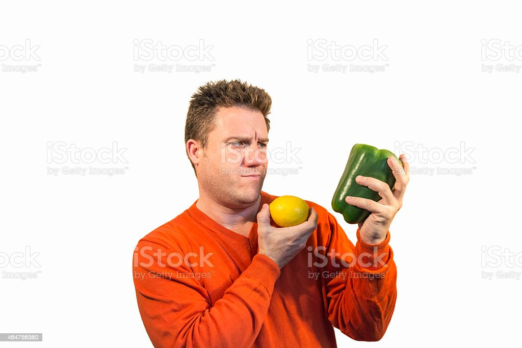 Thoughtful man holding fruits and vegetables stock photo