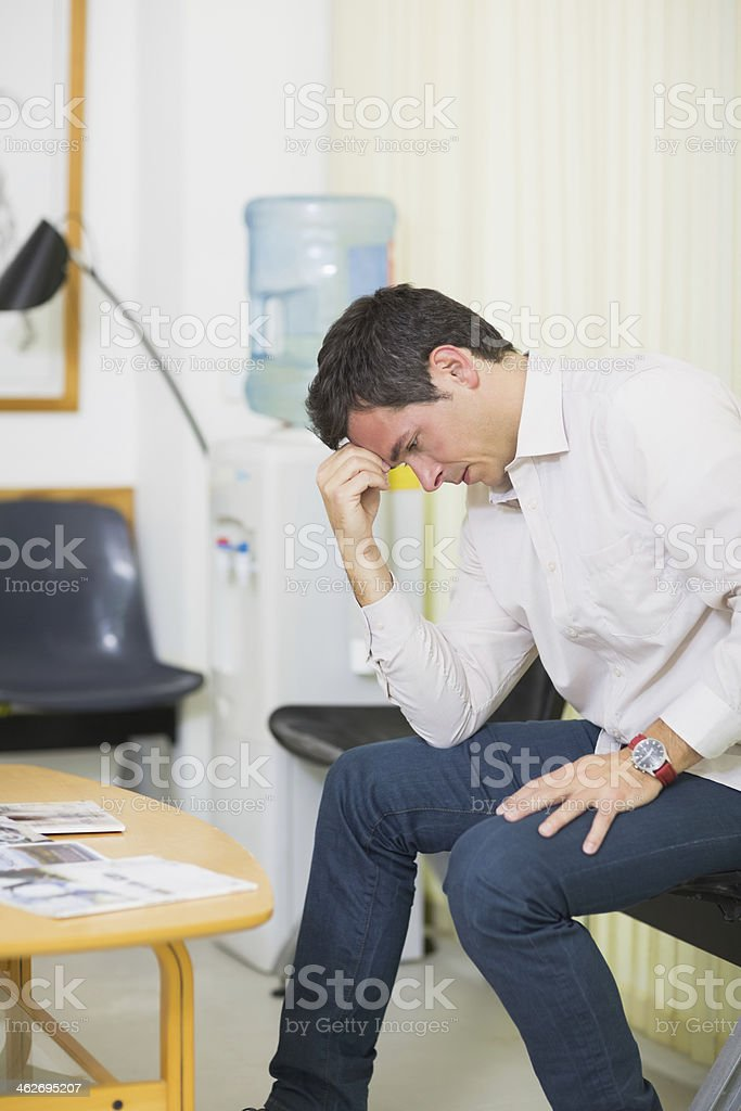 Thoughtful man holding his head in a waiting room stock photo