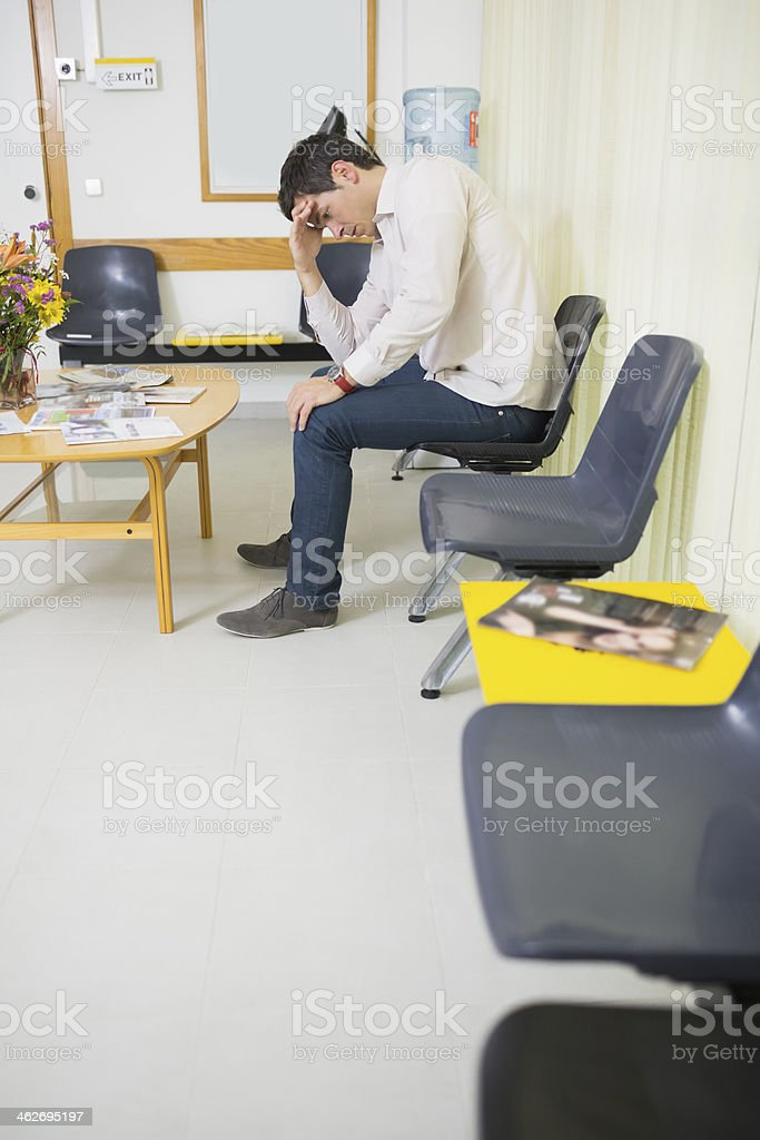 Thoughtful man looking down while sitting in a waiting room stock photo