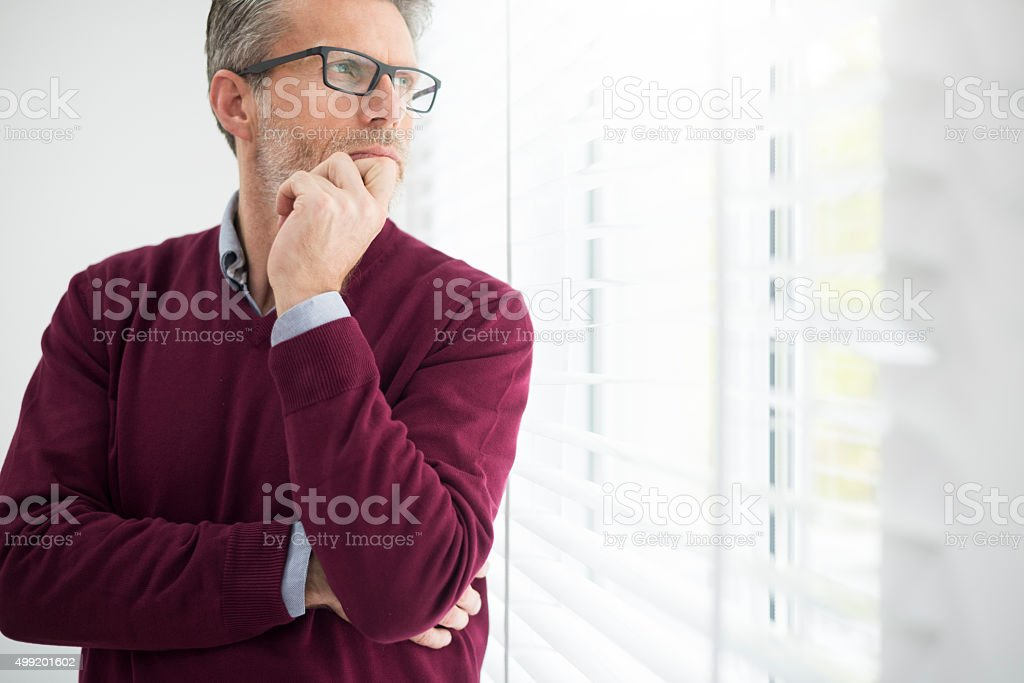 Thoughtful man looking through the window stock photo
