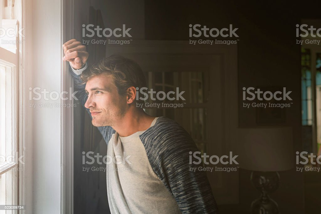 A side view photo of young man looking through window. Thoughtful...