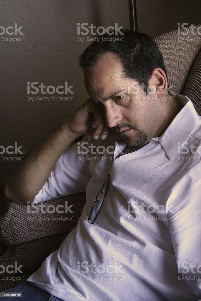 Homme pensif assis et lisant photo libre de droits