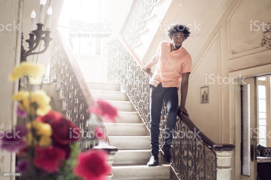 Thoughtful man standing on steps at home stock photo