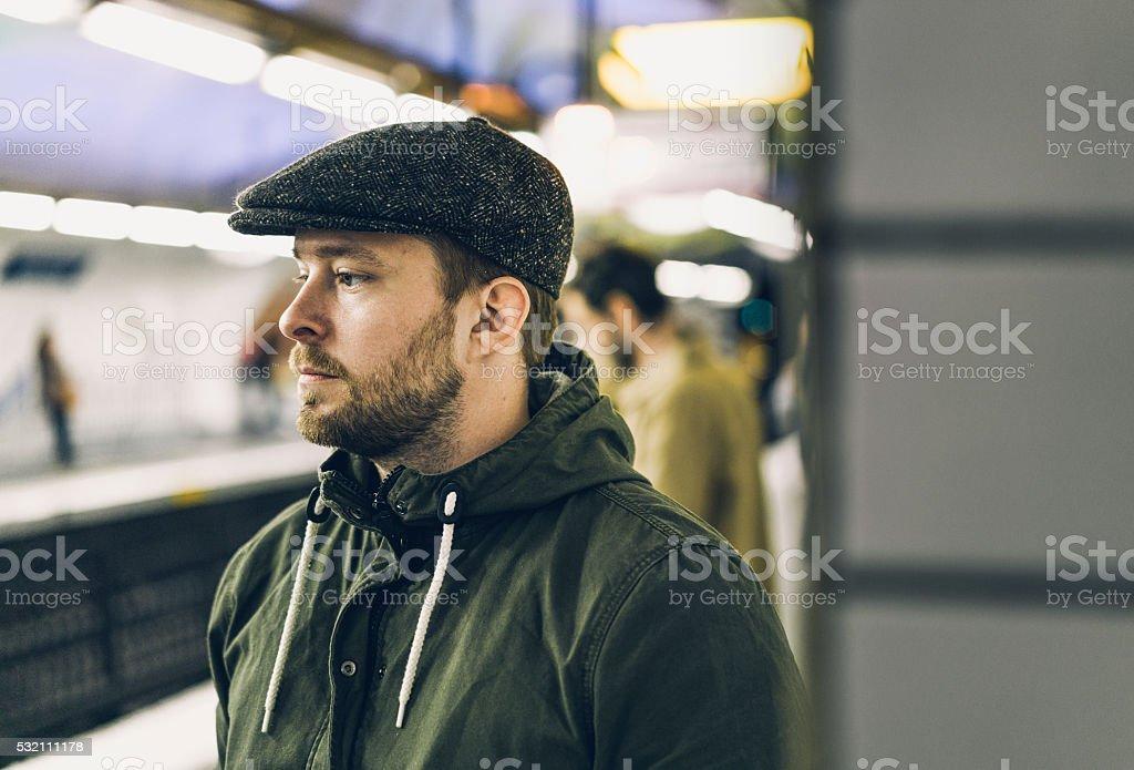 Thoughtful man wearing cap at railroad station stock photo