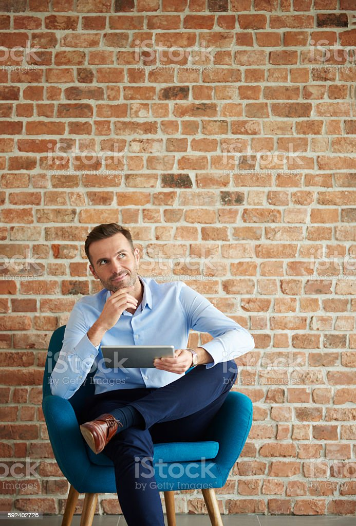 Thoughtful man with digital tablet stock photo