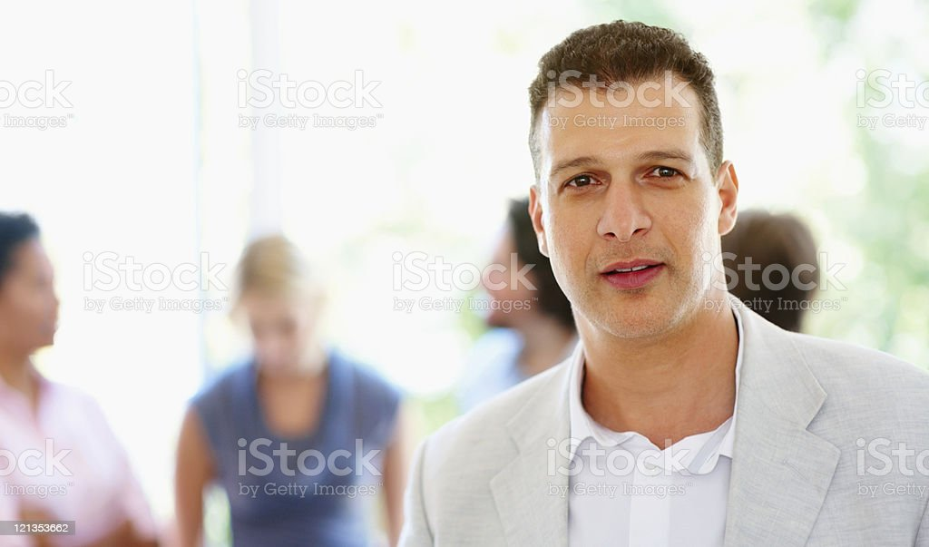 Thoughtful man with group in background stock photo