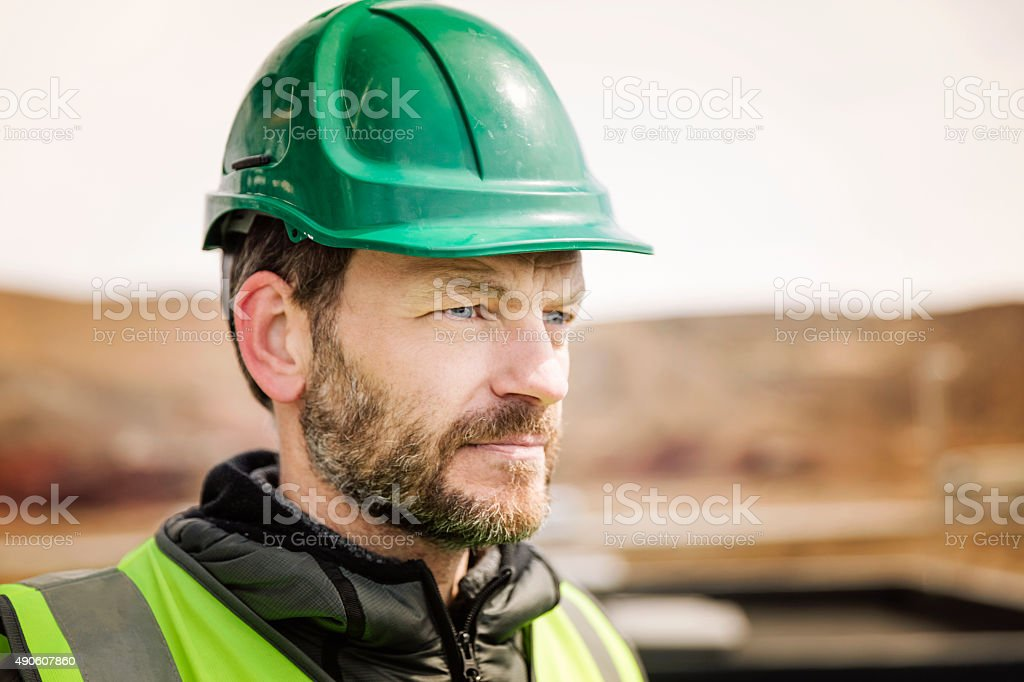 Thoughtful manual worker outside factory stock photo