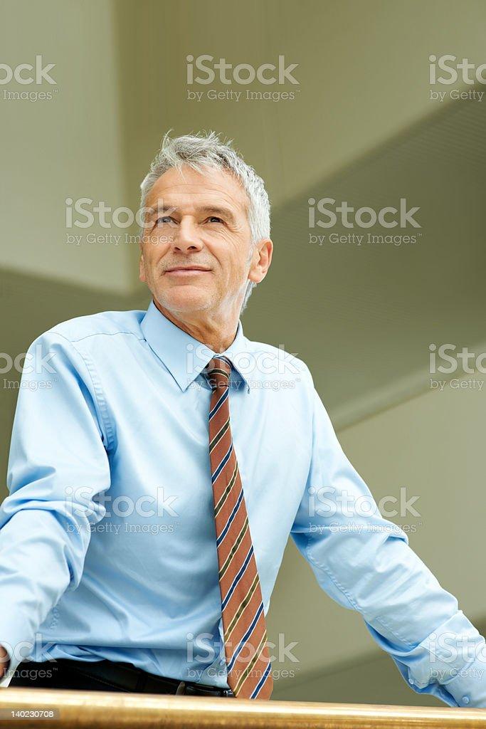 Thoughtful mature businessman looking away stock photo