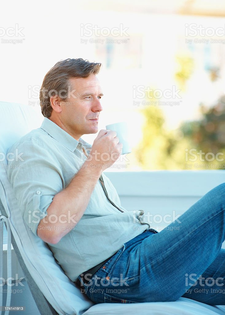 Thoughtful mature man drinking a cup of coffee outdoors stock photo