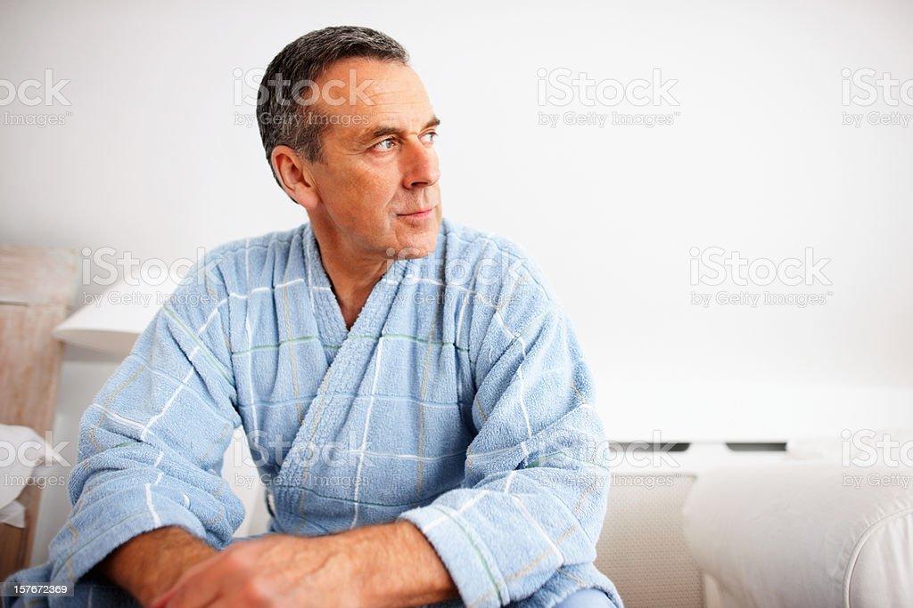 Thoughtful mature man wearing bathrobe while looking away royalty-free stock photo