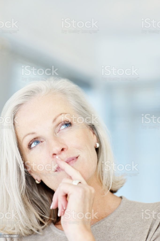 Thoughtful mature woman looking up at copy space royalty-free stock photo