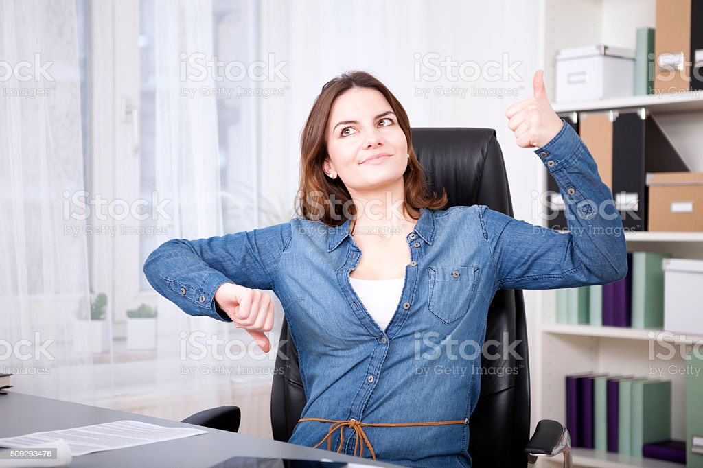Thoughtful Office Woman Showing Thumbs Up and Down stock photo