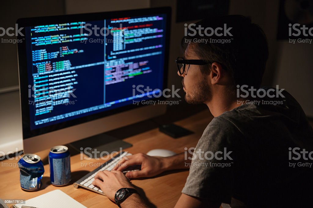 Thoughtful programmer coding in the evening at home stock photo
