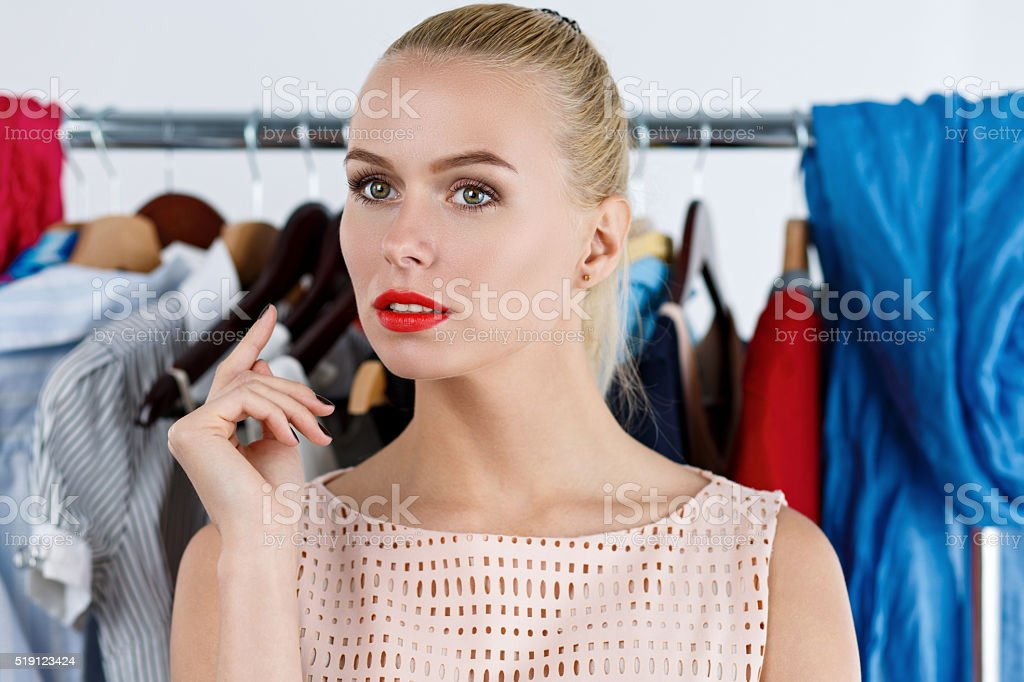 Thoughtful sad beautiful blonde woman standing near wardrobe rac stock photo