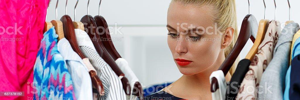 Thoughtful sad blonde woman stand near wardrobe rack stock photo