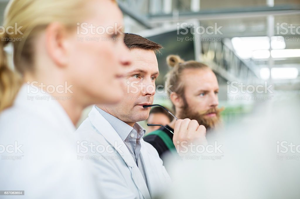 Thoughtful scientist with farm workers in greenhouse stock photo