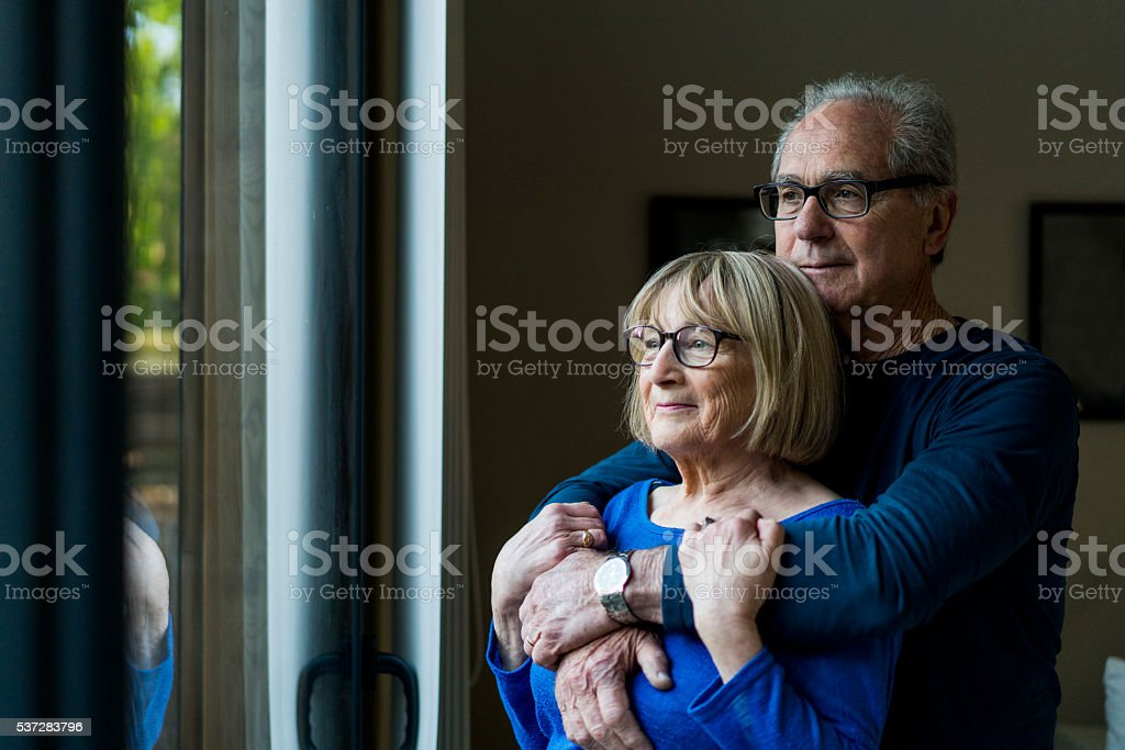 Thoughtful senior couple looking through window stock photo