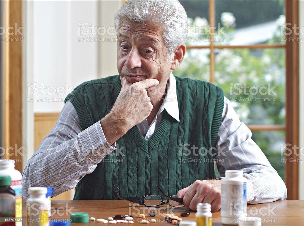 Thoughtful senior man looks at his many pills royalty-free stock photo