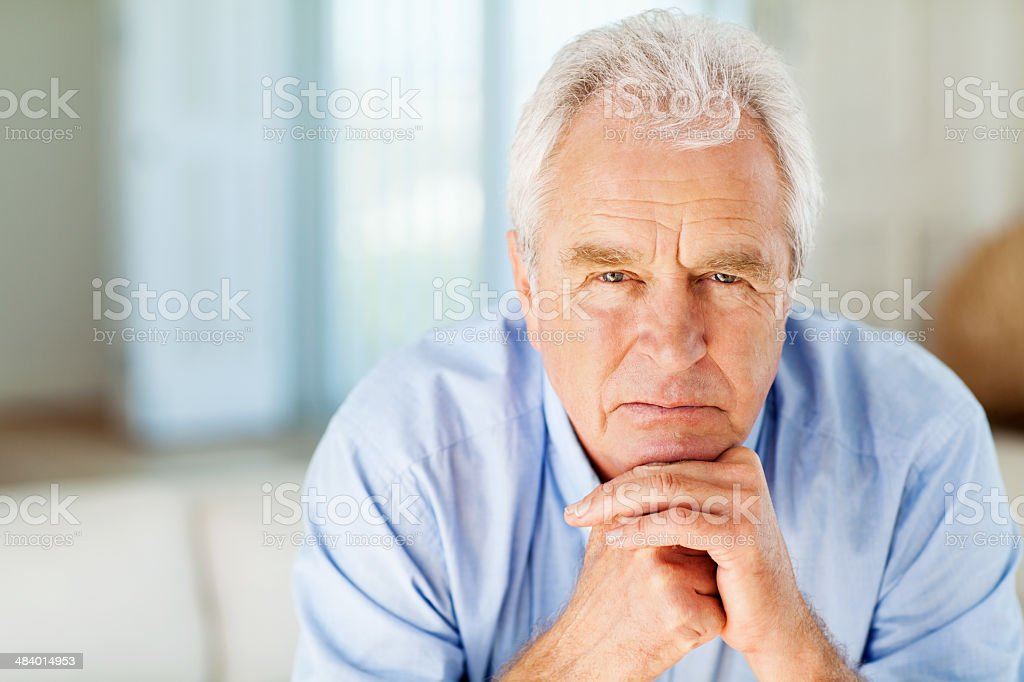 Thoughtful Senior Man With Hand On Chin At Home stock photo