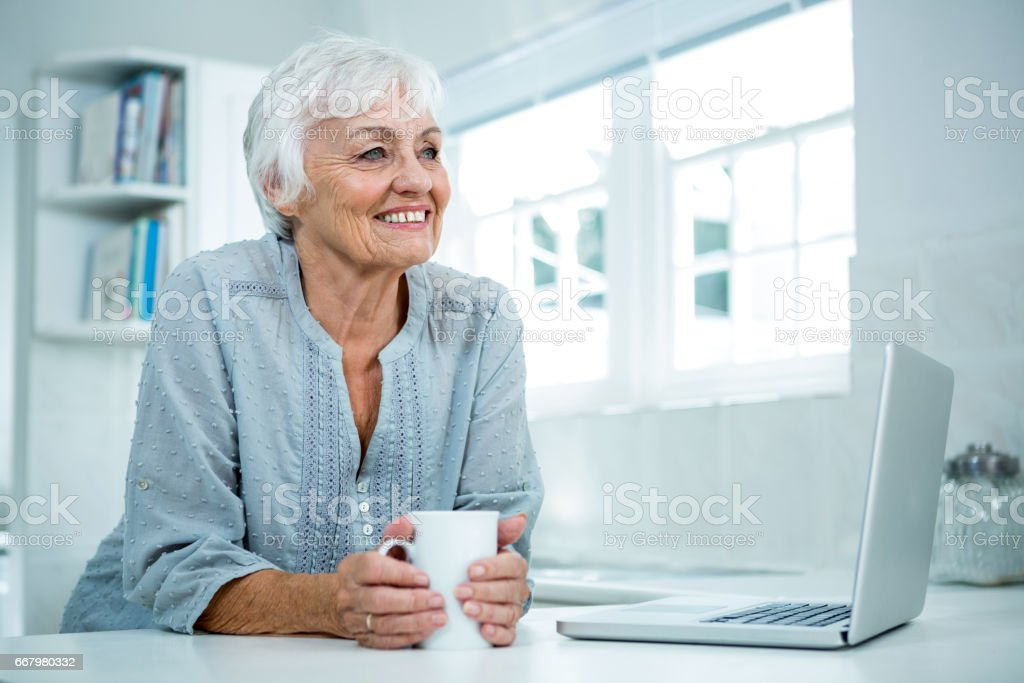Thoughtful senior woman with coffee mug stock photo