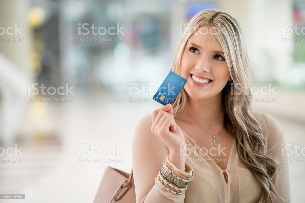 Thoughtful shopping woman holding a credit card stock photo