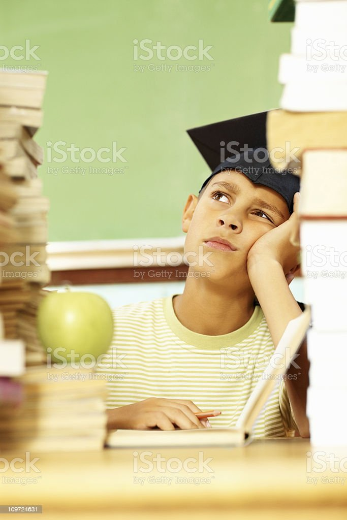 Thoughtful studious boy sitting surrounded with books royalty-free stock photo