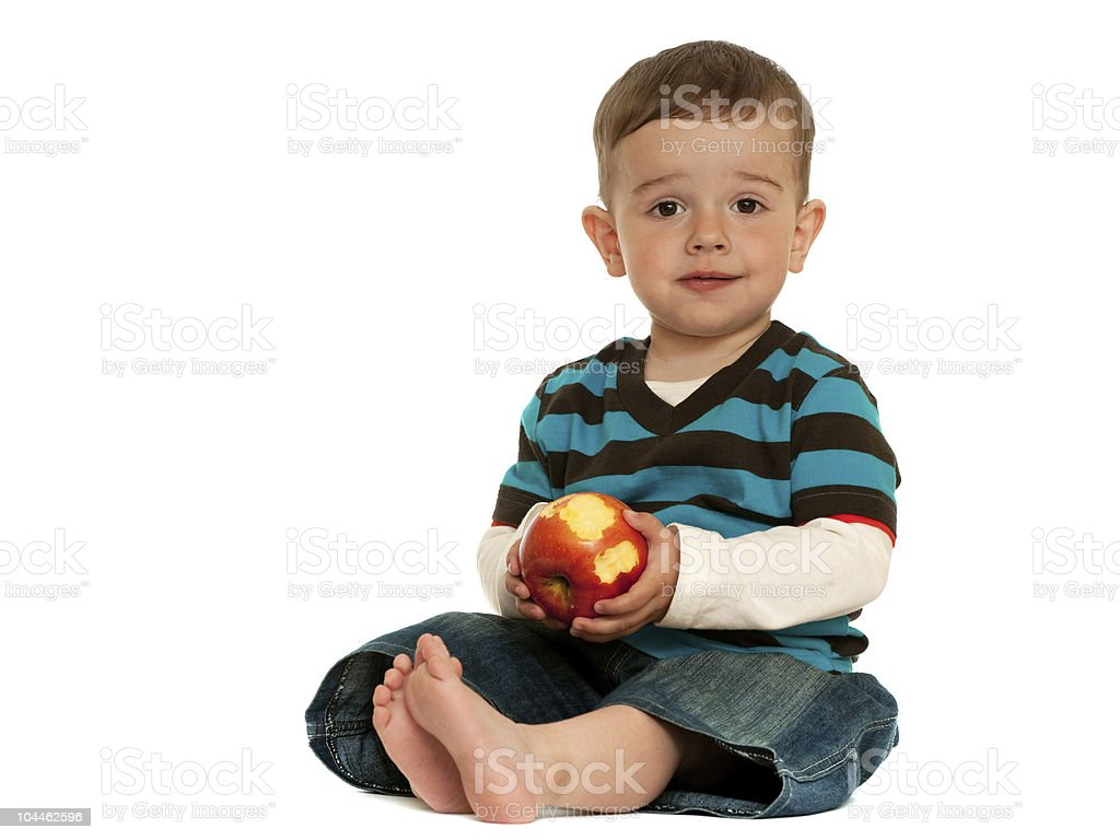 Thoughtful toddler with a red apple royalty-free stock photo