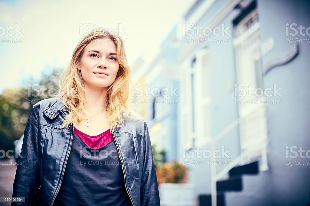 Thoughtful trendy young woman with blond hair outdoors on street stock photo