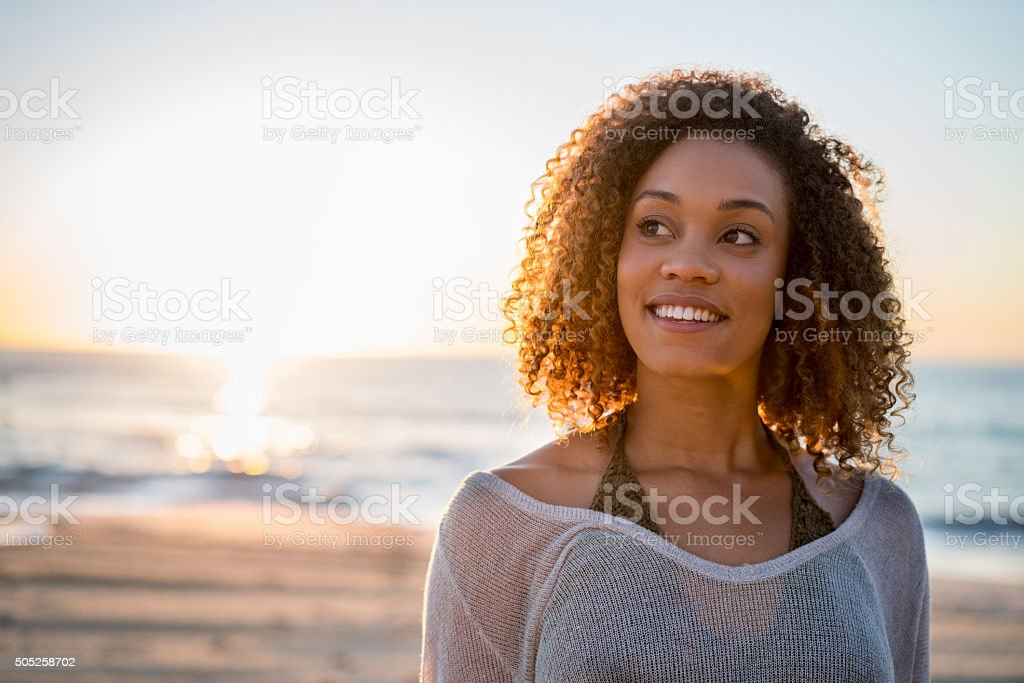 Thoughtful woman at the beach stock photo