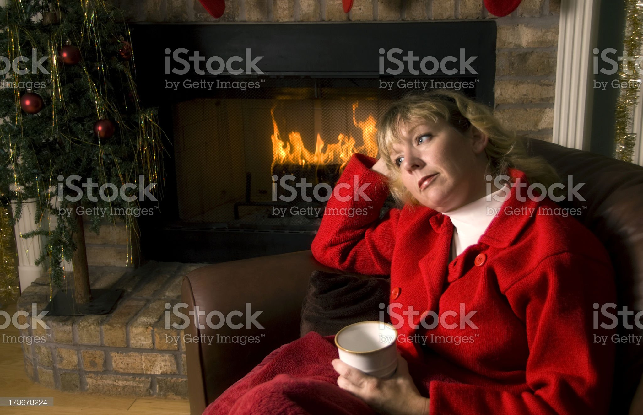 Thoughtful woman by the Fireplace at Christmas royalty-free stock photo
