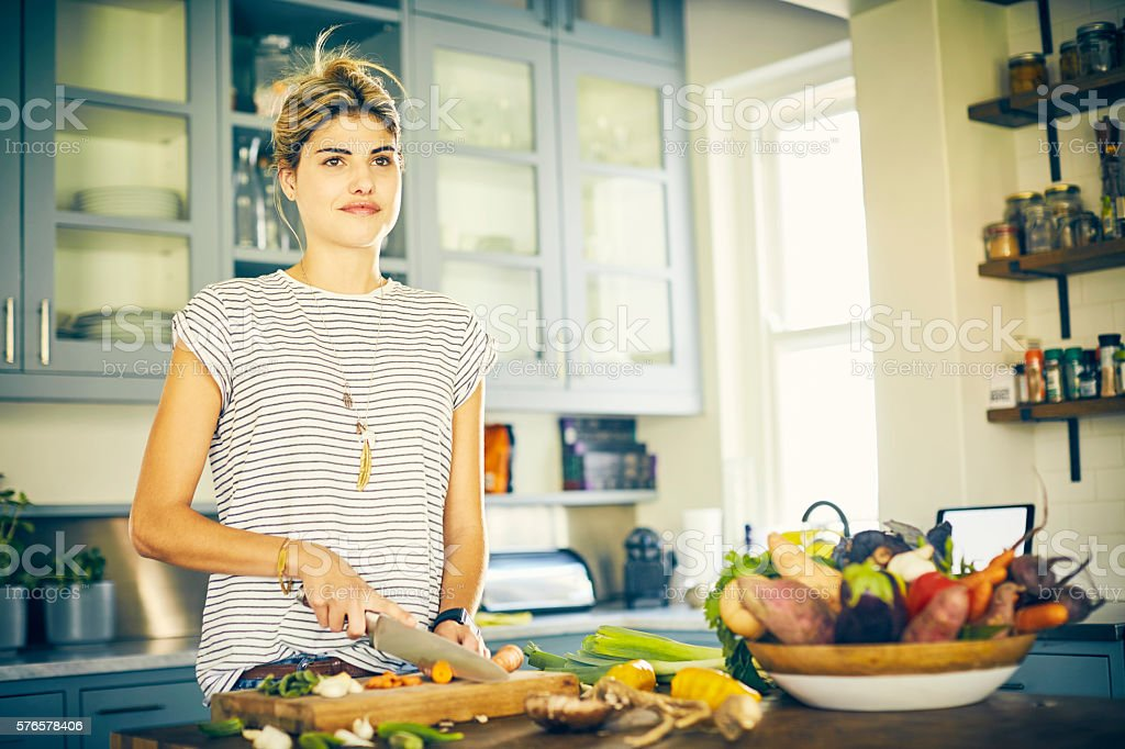 Thoughtful woman cutting carrot in kitchen stock photo