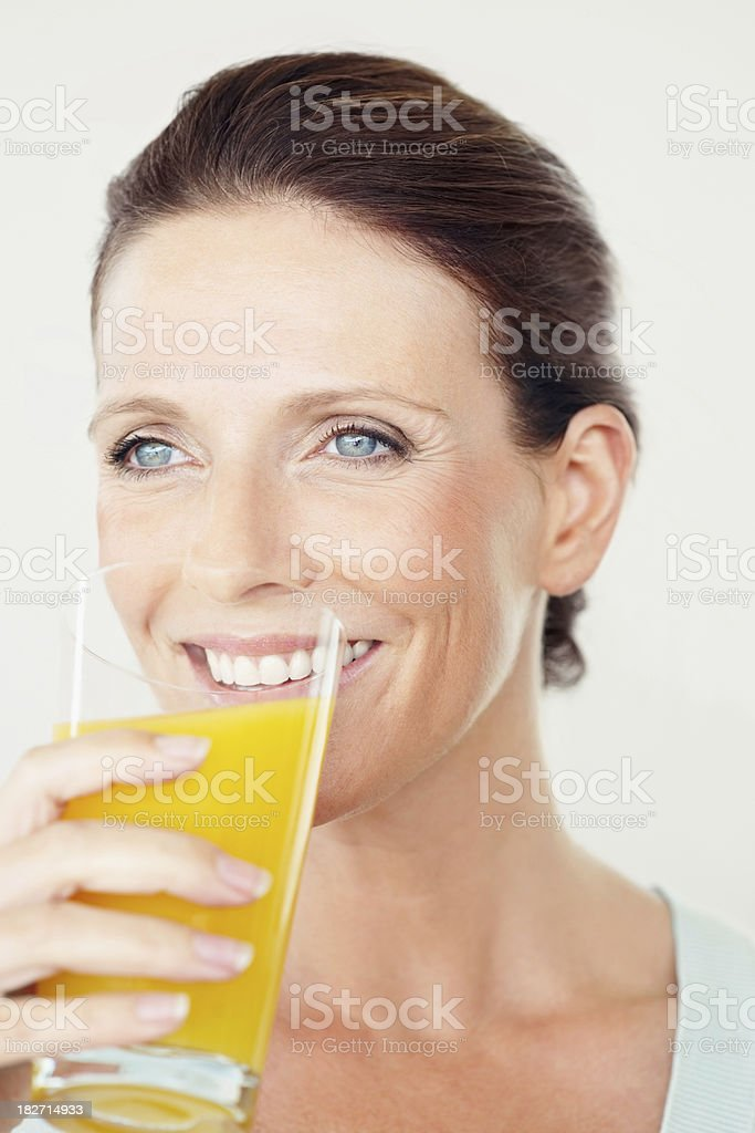 Thoughtful woman drinking a glass of orange juice royalty-free stock photo