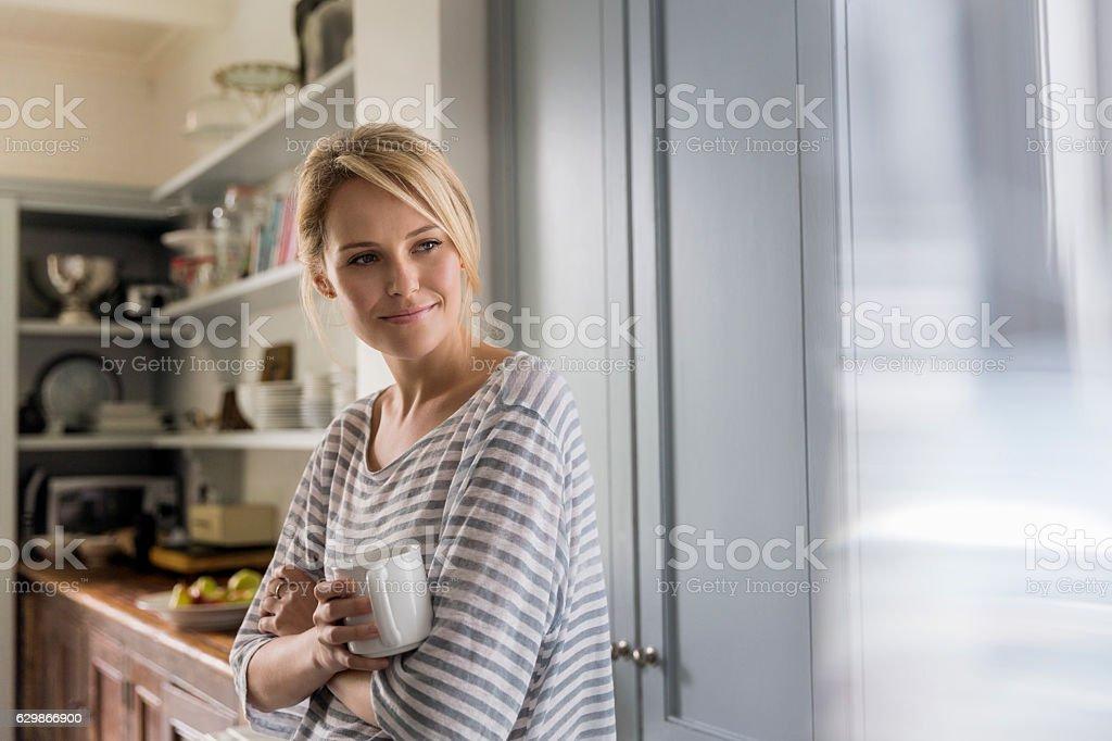 Thoughtful woman holding coffee mug by window stock photo