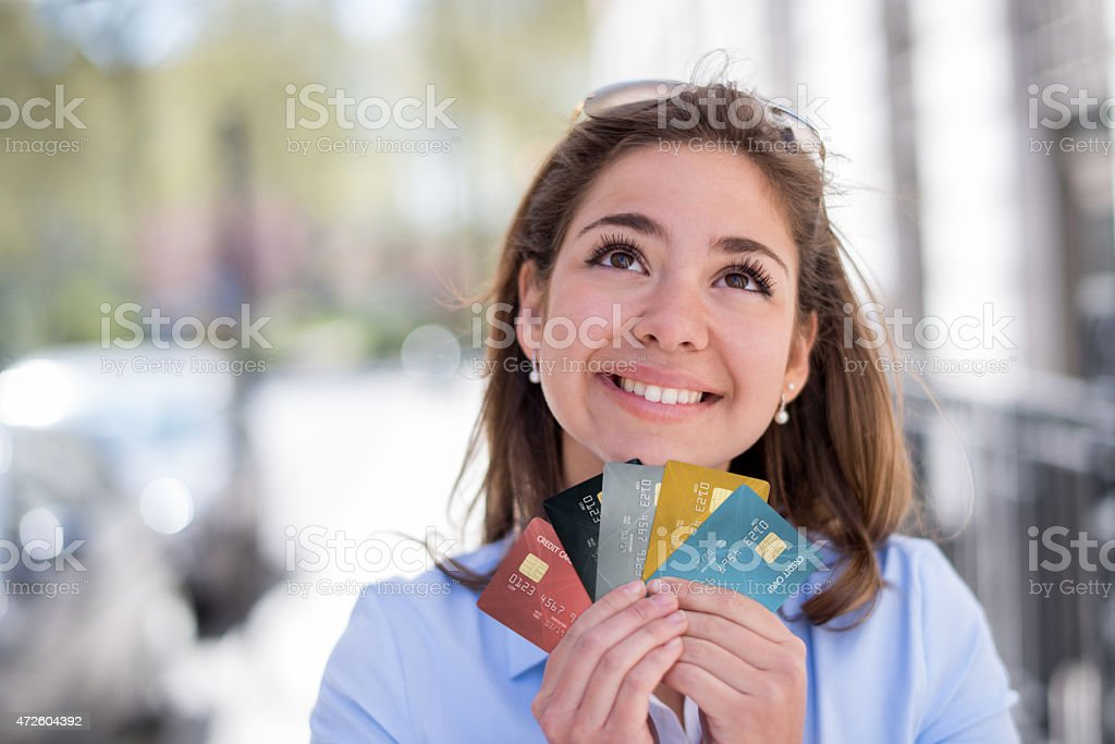 Thoughtful woman holding credit cards stock photo