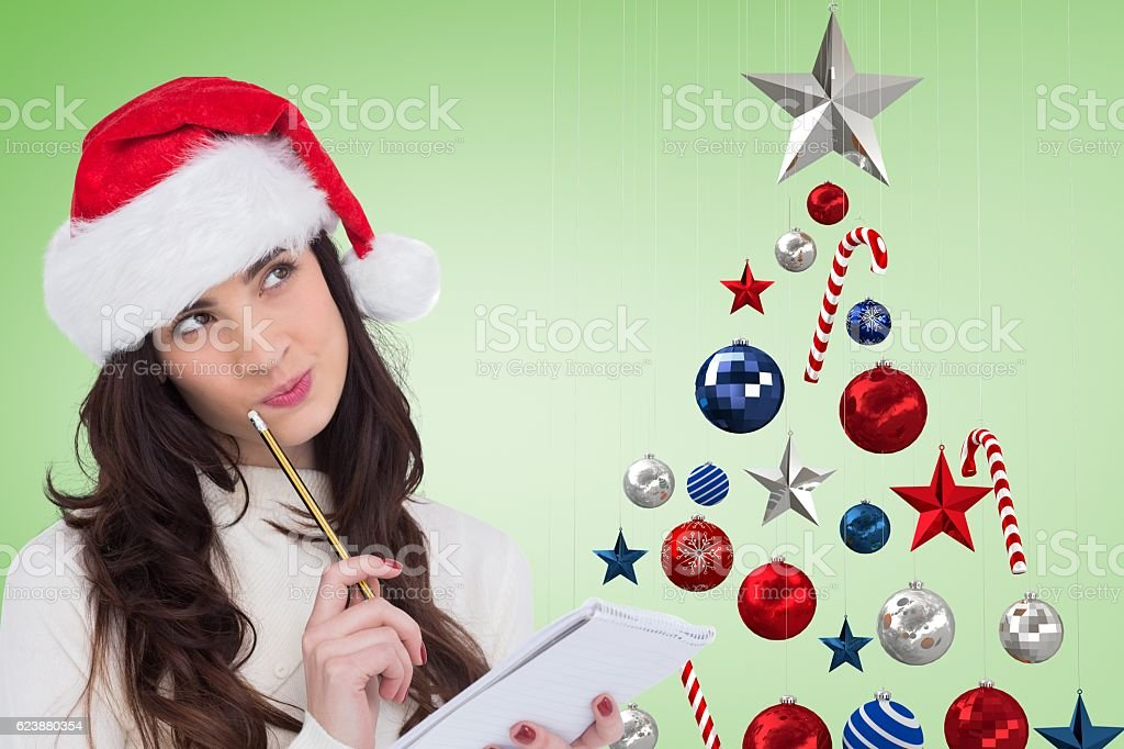 Thoughtful woman in santa hat holding a notepad stock photo
