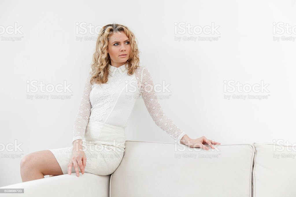 Thoughtful woman in white dress sitting on sofa armrest stock photo