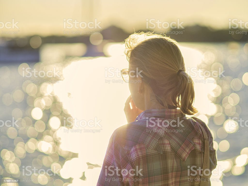 Thoughtful woman looking at lake with bokeh reflections stock photo