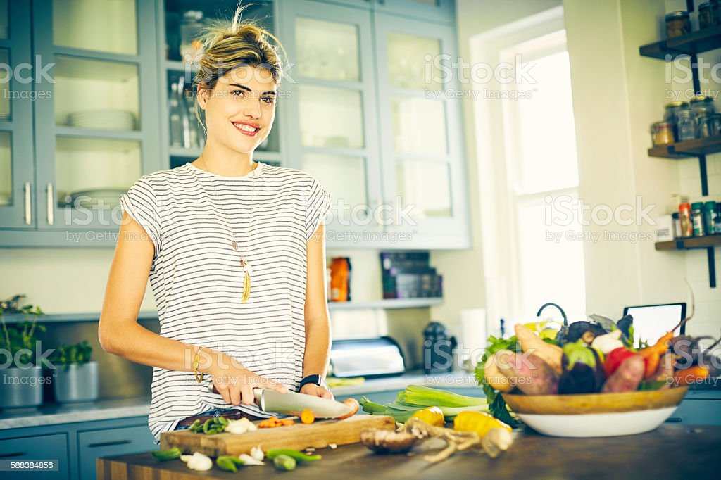 Thoughtful woman smiling while cutting carrot in kitchen stock photo