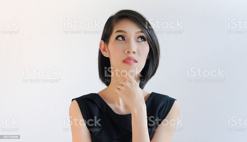 Thoughtful woman thinking, touching her chin and looking up stock photo
